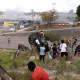 Pessoas se escondem atrás de uma rocha durante confrontos na fronteira venezuelana, em Pacaraima - Foto: REUTERS / Ricardo Moraes