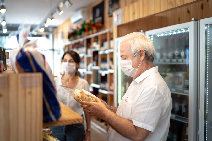 Senior couple buying with face mask at store