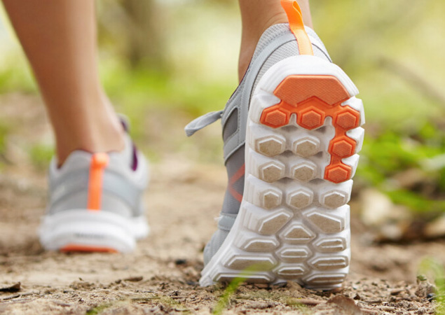 Sports, fitness, nature and healthy lifestyle concept. Young female runner wearing sneakers or running shoes while hiking or jogging in park on sunny day. Cross country or trail woman runner outdoors